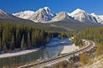 Railway tracks beside Bow River in Banff National Park in winter with beautiful mountain range in the background, Alberta, Canada.
