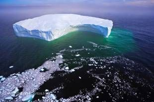 This photo shows a huge iceberg with a floating ice trail in the Strait of Belle Isle off the Labrador coast, Canada.