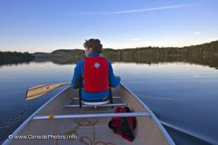 A female is canoeing, one of the popular outdoor activities in Algonquin Provincial Park, on one of the many wilderness lakes inside the park boundary in Ontario, Canada.