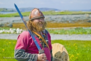 Viking dressed in original viking cloth with a sword and a helmet, at L'Anse aux Meadows National Historic Park, Newfoundland