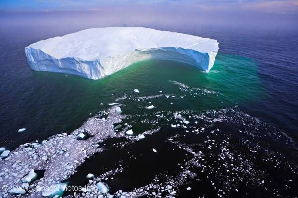 photo of Aerial photo global warming breaking off iceberg Labrador